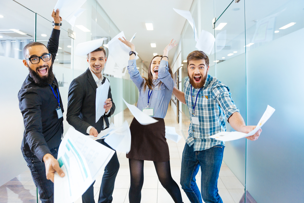 Group of joyful excited business people throwing papers and having fun in office-1